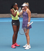 United States' Coco Gauff, left, and compatriot Caty McNally talk in their third round doubles match against Japan's Shuko Aoyama and Ena Shibahara at the Australian Open tennis championship in Melbourne, Australia, Monday, Jan. 27, 2020. (AP Photo/Dita Alangkara)
