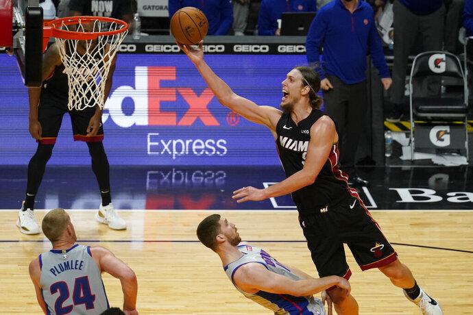 Miami Heat forward Kelly Olynyk (9) drives top the basket over Detroit Pistons guard Svi Mykhailiuk (19) during the second half of an NBA basketball game, Monday, Jan. 18, 2021, in Miami. (AP Photo/Marta Lavandier)