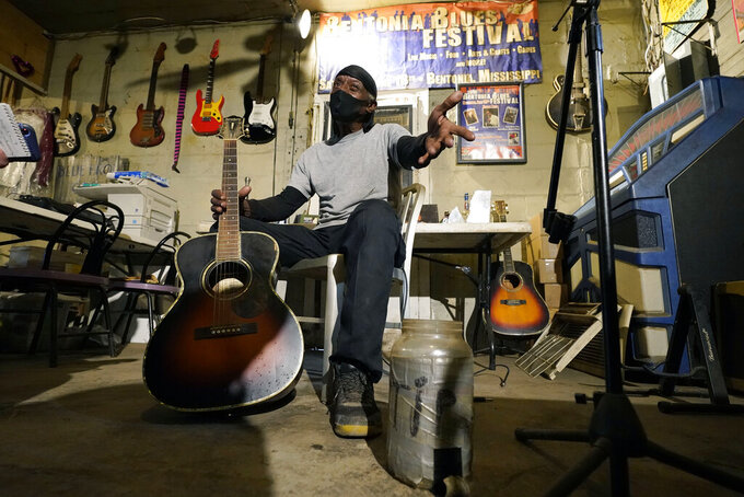 """Bluesman Jimmy """"Duck"""" Holmes gestures as he speaks of the area musicians he learned the style of the Bentonia Blues from at his Blue Front Cafe in Bentonia, Miss., Jan. 21, 2021. Holmes' ninth album, """"Cypress Grove,"""" has earned a Grammy nomination for the Best Traditional Blues Album. (AP Photo/Rogelio V. Solis)"""