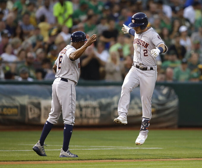 Houston Astros' Alex Bregman, right, celebrates with third base coach Gary Pettis after hitting a two-run home run off Oakland Athletics' Mike Fiers during the fourth inning of a baseball game Thursday, Aug. 15, 2019, in Oakland, Calif. (AP Photo/Ben Margot)
