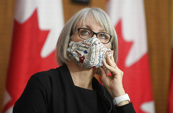 Minister of Health Patty Hajdu uses a translation headset as she listens to a speaker via video conference at a news conference Tuesday, Dec. 1, 2020, in Ottawa. (Adrian Wyld/The Canadian Press via AP)