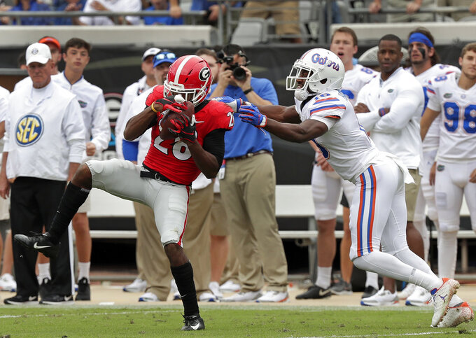 Georgia defensive back Tyrique McGhee, left, intercepts a pass intended for Florida wide receiver Josh Hammond, right, during the first half of an NCAA college football game Saturday, Oct. 27, 2018, in Jacksonville, Fla. (AP Photo/John Raoux)