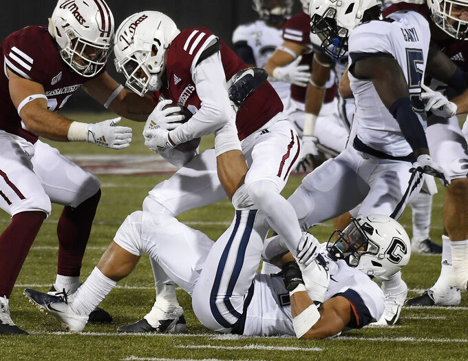 Massachusetts cornerback Isaiah Rodgers (9) is pulled down by Connecticut linebacker Ian Swenson (44) during the second half of an NCAA college football game, Saturday, Oct. 26,, 2019, in Amherst, Mass. (AP Photo/Jessica Hill)