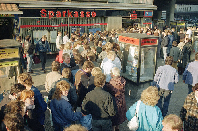 FILE - In this Nov. 10, 1989, file photo East Berliners queue outside a West Berlin bank to receive the 100-Deutsche-Mark