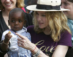 FILE- In this April 19, 2007 file photo, U.S. singer Madonna carries her Malawian adopted son David Banda in the village of Masekese, Malawi. The Queen of Pop is also a soccer mom and she's getting ever more involved in the beautiful game. Madonna has plans to open a soccer academy in Malawi, inspired by her adopted son David Banda who has ambitions to be a professional player and is at Portuguese club Benfica's youth academy. (AP Photo/Karel Prinsloo, file)