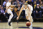 Oklahoma State guard Avery Anderson III (0) and West Virginia guard Sean McNeil (22) scramble for the ball during the first half of an NCAA college basketball game Tuesday, Feb. 18, 2020, in Morgantown, W.Va. (AP Photo/Kathleen Batten)
