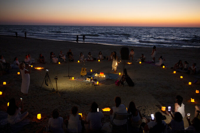 Women take part in a Tashlich ceremony, where they wrote down things they want to release before casting them into a fire, on the beach in Tel Aviv, Israel, Tuesday, Sept. 14, 2021. Tashlich, which means 'to cast away' in Hebrew, is the practice by which Jews go to a large flowing body of water and symbolically 'throw away' their sins by throwing a piece of bread, or similar food, into the water before the Jewish holiday of Yom Kippur, the holiest day in the Jewish year which starts at sundown Wednesday. (AP Photo/Maya Alleruzzo)