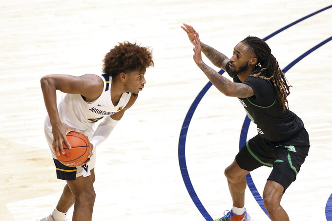 West Virginia guard Miles McBride (4) is defended by North Texas guard James Reese (0) during the second half of an NCAA college basketball game Friday, Dec. 11, 2020, in Morgantown, W.Va. (AP Photo/Kathleen Batten)