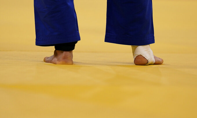 Kim Won-jin, of South Korea, stands on the mat with his ankle taped while competing against Yeldos Smetov, of Kazakhstan, during their mens 60kg quarterfinals judo match at the 2020 Summer Olympics, Saturday, July 24, 2021, in Tokyo, Japan. (AP Photo/Jae C. Hong)