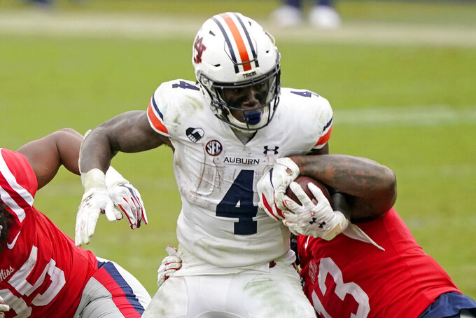 Auburn running back Tank Bigsby (4) fights off a tackle attempt by Mississippi linebacker Sam Williams (13) during the second half of an NCAA college football game in Oxford, Miss., Saturday, Oct. 24, 2020.  (AP Photo/Rogelio V. Solis)
