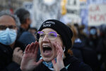 A protester shouts during a demonstration security law that would restrict sharing images of police, Saturday, Nov. 28, 2020 in Paris. Critics of a proposed French security law in France that would restrict sharing images of police are gathering across the country in protest. Civil liberties groups and journalists are concerned that the measure will stymie press freedoms and allow police brutality to go undiscovered and unpunished. (AP Photo/Francois Mori)
