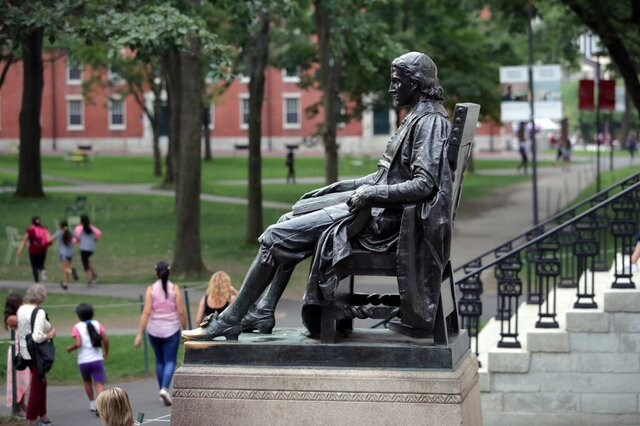 FILE - In this Aug. 13, 2019, file photo, students walk past the statue of John Harvard in Harvard Yard at Harvard University in Cambridge, Mass. U.S. Education Secretary Betsy DeVos on Wednesday, April 22, 2020, urged the nation's richest colleges, including Harvard, to reject federal funding that was allotted to them in the government's multi-trillion dollar coronavirus rescue package. (AP Photo/Charles Krupa, File)