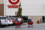Shoppers take purchases to their vehicle in the parking lot of a Target store, Tuesday, Aug. 4, 2020, in Marlborough, Mass. (AP Photo/Bill Sikes)