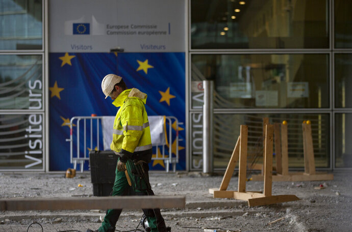 FILE - In this Wednesday, Oct. 9, 2019 file photo, a construction worker stands in front of a door with the EU stars at EU headquarters in Brussels. The Brexit process shook the EU foundations and laid bare the need for much-delayed renovations, but tthe question now is where to start the revamp and who is going to foot the bill. (AP Photo/Virginia Mayo, File)