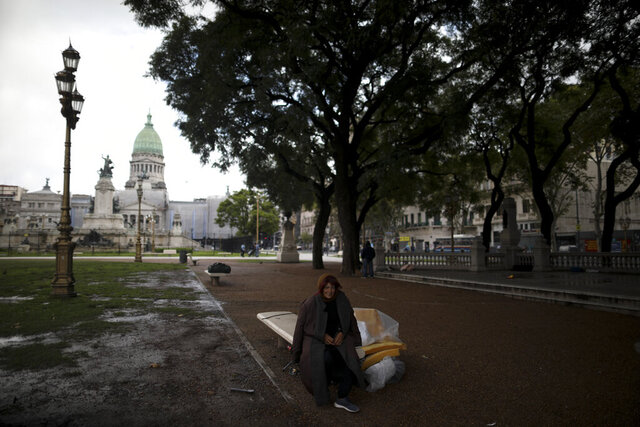 Angelina Stoker, a homeless woman, rests on the bench where she sleeps at an empty park outside Congress in Buenos Aires, Argentina, Wednesday, April 1, 2020. The Argentine government ordered a forced lock down to help contain the spread of the new coronavirus.  (AP Photo/Natacha Pisarenko)