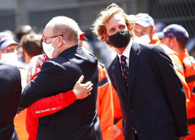 Prince Albert II of Monaco, center, embraces Ferrari driver Charles Leclerc of Monaco prior to the start of the Monaco Grand Prix at the Monaco racetrack, in Monaco, Sunday, May 23, 2021. (Sebastien Nogier, Pool via AP)