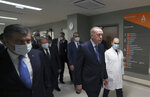 In this photo provided by the Turkish Presidency, Turkey's President Recep Tayyip Erdogan, front center, arrives to attend the inauguration ceremony for Basaksehir Pine and Sakura City Hospital, in Istanbul, Thursday, May 21, 2020. Japanese Prime Minister Shinzo Abe who participated by videoconference the ceremony has called for international cooperation against the new coronavirus, saying any drug or vaccine developed against the virus must be made