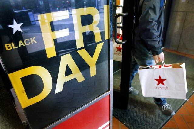 FILE - In this Nov. 29, 2019 file photo, a shopper leaves Macy's in Boston on Black Friday. There are only a few days left until Black Friday shopping events — and even less time until Thanksgiving, when some Black Friday sales actually kick off. But you can still prepare your gift list and come up with a shopping strategy before the promotions start.  (AP Photo/Michael Dwyer, File)
