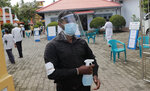 A Sri Lankan polling officer wearing mask and face shield stands holding a sanitizer sprayer at the entrance to a polling center during the parliamentary election in Colombo, Sri Lanka, Wednesday, Aug. 5, 2020. The election was originally scheduled for April but was twice postponed due to the COVID-19 pandemic. (AP Photo/Eranga Jayawardena)