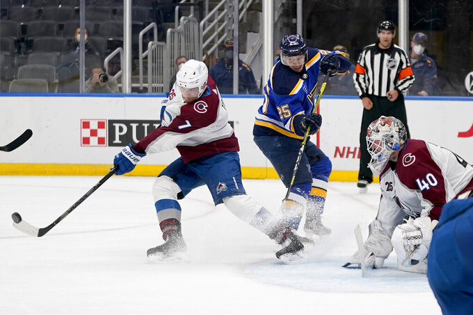 Colorado Avalanche's Devon Toews (7) clears a puck as goaltender Devan Dubnyk (40) and St. Louis Blues' Jordan Kyrou (25) watch during the second period of an NHL hockey game Thursday, April 22, 2021, in St. Louis. (AP Photo/Jeff Roberson)