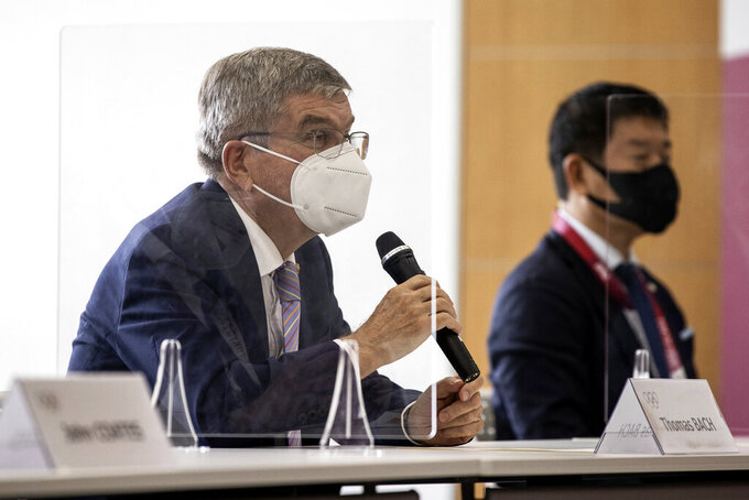 IOC President Thomas Bach, left, speaks to Tokyo 2020 President Seiko Hashimoto, not in photo, during their meeting at the Tokyo 2020 Headquarters Tuesday, July 13, 2021 in Tokyo, Japan. Bach appeared in public on Tuesday for the first time since arriving in Tokyo last week with the pandemic-postponed Olympics opening in just 10 days.  (Takashi Aoyama/Pool Photo via AP)