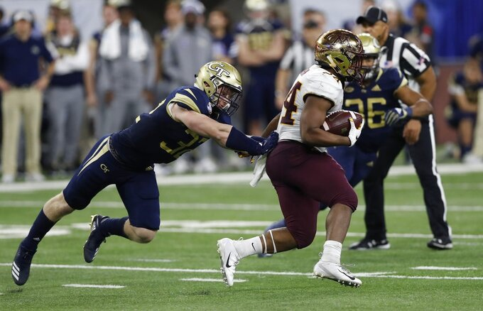 Georgia Tech linebacker David Curry, left, attempts to stop Minnesota running back Mohamed Ibrahim during the second half of the Quick Lane Bowl NCAA college football game, Wednesday, Dec. 26, 2018, in Detroit. (AP Photo/Carlos Osorio)