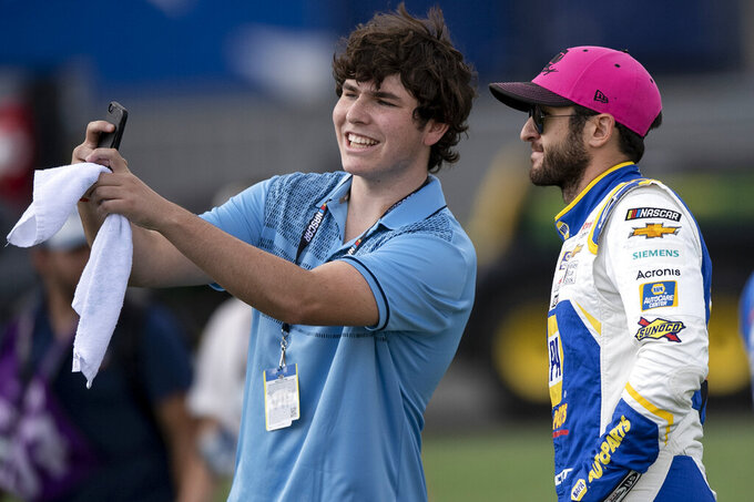 Chase Elliott (9) takes a selfie with a fan prior to a NASCAR Cup Series auto racing race at Charlotte Motor Speedway, Monday, Oct. 11, 2021, in Concord, N.C. (AP Photo/Matt Kelley)