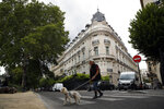 A man walks his dog next to an apartment building owned by Jeffrey Epstein in the 16th district in Paris, Tuesday, Aug. 13, 2019. France's government wants prosecutors to open an investigation into Jeffrey Epstein's links to France following his death in a Manhattan jail cell. U.S. authorities say Epstein had a residence in Paris and used a fake Austrian passport to travel to France in the 1980s. (AP Photo/Francois Mori)