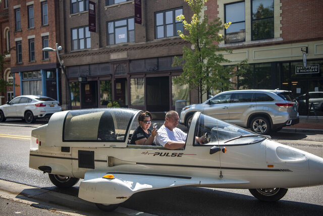 Andy and Ginger Segar cruise down Michigan Avenue in their Pulse autocycle on Friday, Aug. 28, 2020, in Battle Creek, Mich. Andy purchased the Owosso Pulse, made by the Owosso Motor Company, from his friend's father, a childhood dream come true.  (Alyssa Keown/Battle Creek Enquirer via AP)