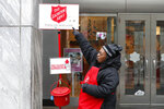 In this Friday, Nov. 15, 2019, photo, bell ringer Carolyn Harper points to two ways to donate via mobile device to the Salvation Army's annual holiday red kettle campaign on Chicago's Magnificent Mile. Cashless shoppers have a new option to give to the Army's red kettle campaign this year using their smartphone. Leaders hope adding Apple and Google payment options will boost fundraising to the campaign, which makes up 10% of The Salvation Army's annual budget. Those donations fund programs providing housing, food and other support to people in poverty. (AP Photo/Charles Rex Arbogast)