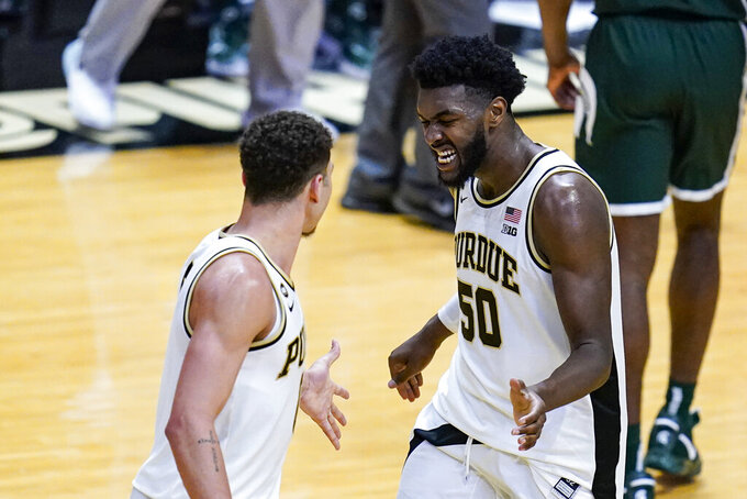 Purdue forward Trevion Williams (50) celebrates with forward Mason Gillis (0) during the second half of an NCAA college basketball game against Michigan State in West Lafayette, Ind., Tuesday, Feb. 16, 2021. Purdue won 75-65. (AP Photo/Michael Conroy)