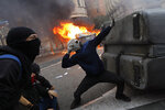 A protestors uses a sling during clashes with police in Barcelona, Spain, Friday, Oct. 18, 2019.The Catalan regional capital is bracing for a fifth day of protests over the conviction of a dozen Catalan independence leaders. Five marches of tens of thousands from inland towns are converging in Barcelona's center for a mass protest. (AP Photo/Bernat Armangue)