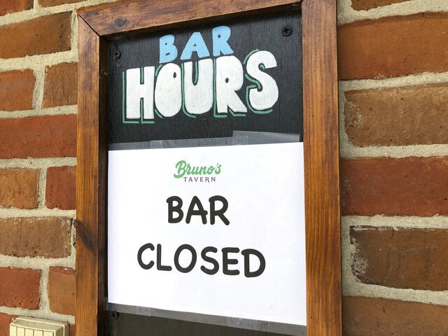 A sign hangs outside Bruno's Tavern in New Orleans on Tuesday, July 14, 2020. Bruno's is one of many bars around the city that shut down under new restrictions the state announced over the weekend to fight the spread of coronavirus. Bars in New Orleans had been allowed to open, with limited capacity, a month earlier when the number of hospitalizations from the virus in Louisiana was in decline. (AP Photo/Kevin McGill)