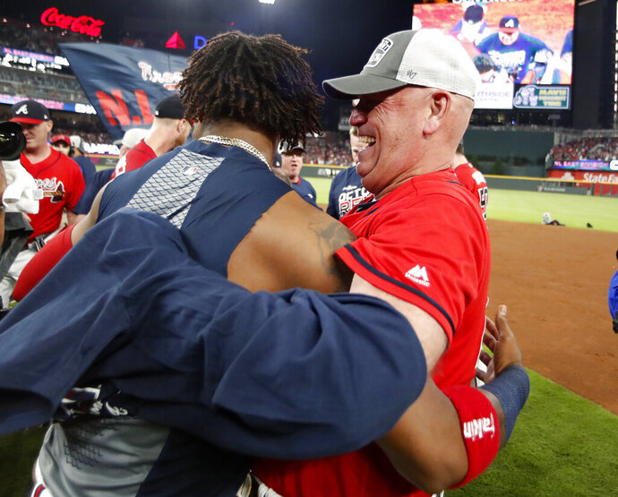 Atlanta Braves manager Brian Snitker (43), right, hugs Ronald Acuna Jr., after defeating the San Francisco Giants in a baseball game to clinch the NL East baseball title Friday, Sept. 20, 2019, in Atlanta. (AP Photo/John Bazemore)
