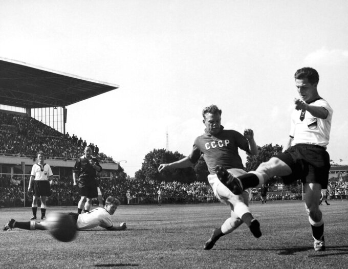 FILE - In this Nov. 24, 1956, file photo, German inside right Rolf K. Geiger, right, gets the ball past a Soviet defender during the Germany vs Russia Olympic Association Football match on the Olympic Park football field in Melbourne, Australia on. Russia won 2-1. (AP Photo/Stuart Heydinger, File)