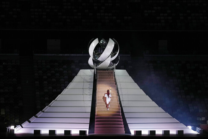 Naomi Osaka climbs stairs to light the Olympic Cauldron during the opening ceremony in the Olympic Stadium at the 2020 Summer Olympics, Friday, July 23, 2021, in Tokyo, Japan. (AP Photo/Kirsty Wigglesworth)