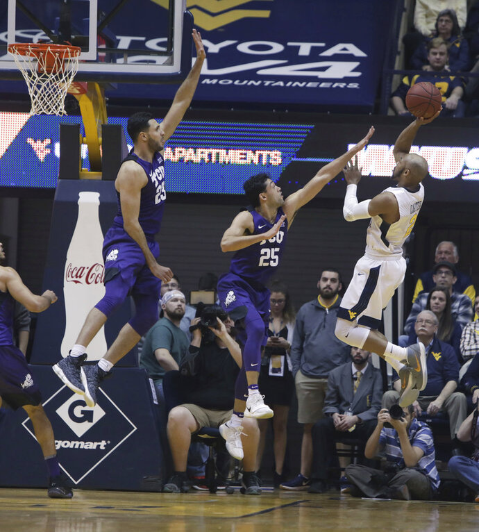 West Virginia guard Jevon Carter (2) shoots while being defended by TCU guard Alex Robinson (25) during the first half of an NCAA college basketball game Monday, Feb. 12, 2018, in Morgantown, W.Va. (AP Photo/Raymond Thompson)