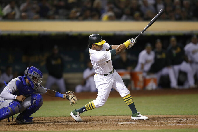 Oakland Athletics' Khris Davis swings for an RBI single off Kansas City Royals' Kevin McCarthy in the eighth inning of a baseball game, Monday, Sept. 16, 2019, in Oakland, Calif. (AP Photo/Ben Margot)