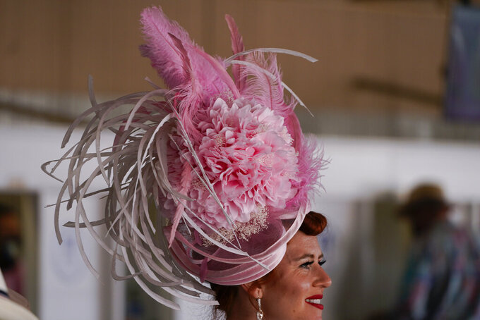 A women walks past wagering windows before the 147th running of the Kentucky Oaks at Churchill Downs, Friday, April 30, 2021, in Louisville, Ky. (AP Photo/Charlie Riedel)