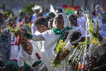 Ethiopians throw grass into a pool of water, as a symbol of riches after the rainy season and to thank the land and water for everything they have provided, as they celebrate the annual Irrecha thanksgiving festival in the capital Addis Ababa, Ethiopia Saturday, Oct. 5, 2019. The annual Irrecha festival of Ethiopia's largest ethnic group, the Oromo, attracted millions from across Ethiopia and was held in the capital for the first time after 150 years on Saturday. (AP Photo/Mulugeta Ayene)