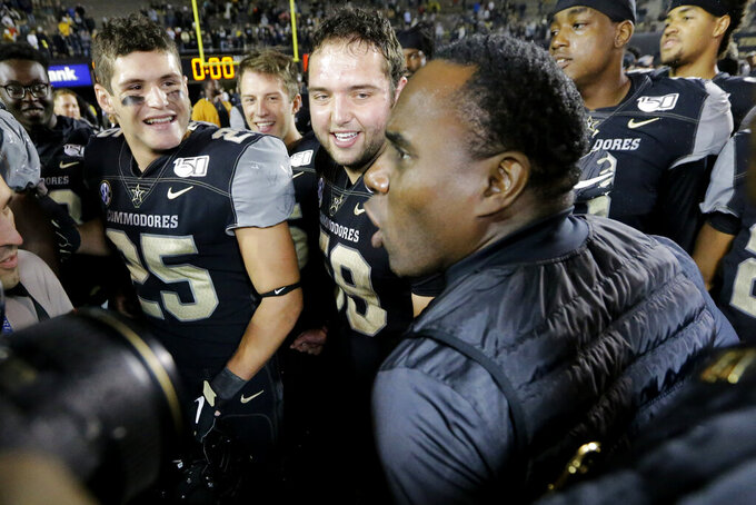 Vanderbilt head coach Derek Mason celebrates with his team, including Mitchell Pryor (25) and Scott Meyer (59), after Vanderbilt upset Missouri in an NCAA college football game Saturday, Oct. 19, 2019, in Nashville, Tenn. Vanderbilt won 21-14. (AP Photo/Mark Humphrey)