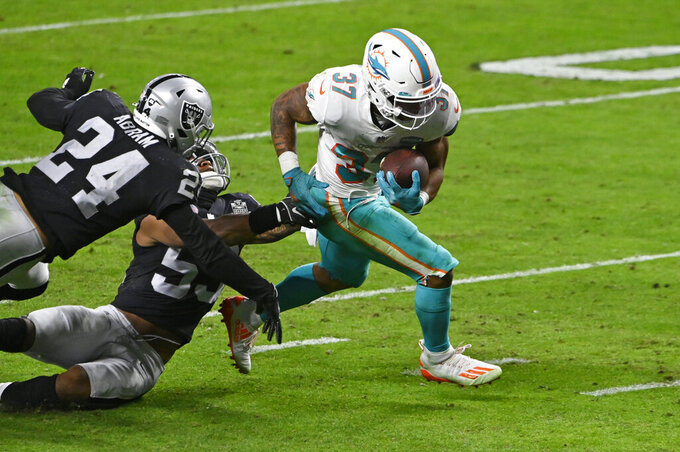 Miami Dolphins running back Myles Gaskin (37) runs in for a touchdown against Las Vegas Raiders strong safety Johnathan Abram (24) during the second half of an NFL football game, Saturday, Dec. 26, 2020, in Las Vegas. (AP Photo/David Becker)