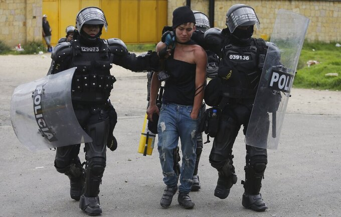 An anti-government protester is detained by police in Gachancipa, Colombia, Friday, May 7, 2021. The protests that began last week over a tax reform proposal continue despite President Ivan Duque's withdrawal of the tax plan on Sunday, May 2. (AP Photo/Ivan Valencia)