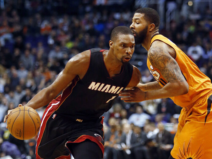 FILE - In this Jan. 8, 2016, file photo, Miami Heat forward Chris Bosh (1) drives on Phoenix Suns forward Markieff Morris during an NBA basketball game in Phoenix. Bosh, who had arguably the biggest rebound and assist in Miami Heat history, will have his No. 1 jersey retired by the franchise on March 26. The Heat made the announcement Monday, Feb. 4, 2019. Bosh played parts of six seasons in Miami, before his career was cut short by recurring issues with blood clots. He last played for the Heat in 2016. (AP Photo/Rick Scuteri, File)