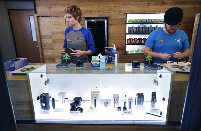 FILE - In this Oct. 17, 2018 file photo patient service associates Savannah Stuitje, left, and Josh Hirst, right, stand at a counter that features a display of vape dispensers, below, at New England Treatment Access medical marijuana dispensary, in Northampton, Mass. Medical marijuana products are set to become exempt from Massachusetts' four-month vaping materials ban. Suffolk Superior Court Judge Douglas Wilkins ruled a week ago that marijuana cultivated for medical use must be exempted from Republican Gov. Charlie Baker's ban starting Tuesday, Nov. 12, 2019. (AP Photo/Steven Senne, File)