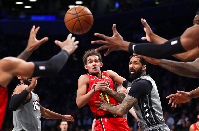 Atlanta Hawks guard Trae Young (11) passes the ball away from Brooklyn Nets forward Wilson Chandler during the first half of an NBA basketball game Saturday, Dec. 21, 2019, in New York. (AP Photo/Noah K. Murray)