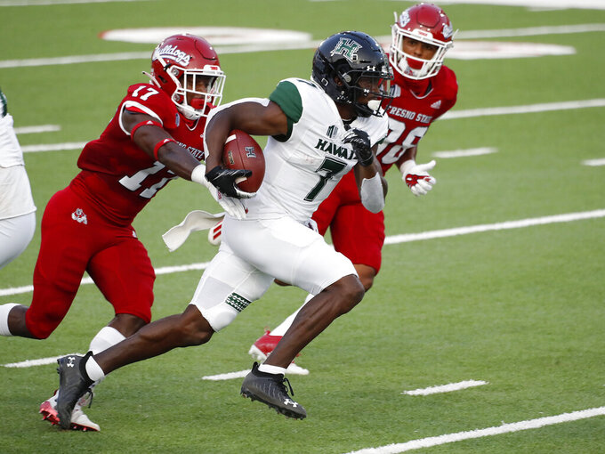 Hawaii running back Calvin Turner runs past Fresno State defensive back Deonte Perry for a long gain during the first half of an NCAA college football game in Fresno, Calif., Saturday, Oct. 24, 2020. (AP Photo/Gary Kazanjian)