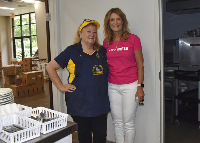 """In this 2020 photo, President and CEO of United Way of SWLA, Denise Durel, right, and volunteer Chef Liz Landers at a food drive in Lake Charles, La. """"Everyday is a new day, everyday is different and we're just taking on the challenges as they're presented to us. Where's the need, what can we do, and let's just do it,"""" said Durel. (American Press via AP)"""