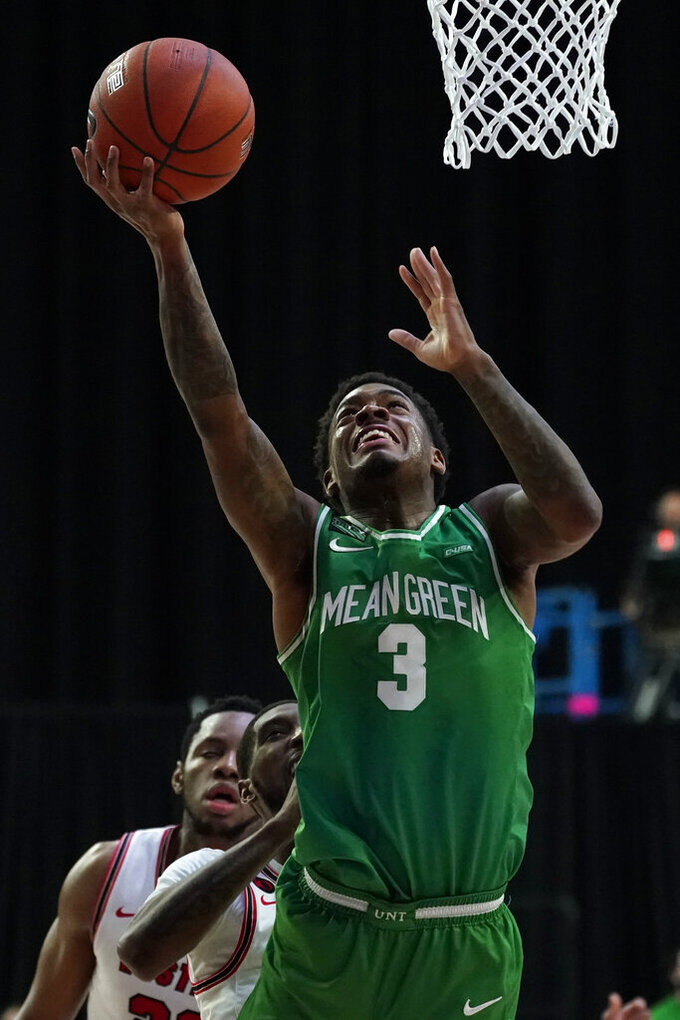 North Texas guard Javion Hamlet (3) shoots ahead of Western Kentucky guard Taveion Hollingsworth during the first half of the championship game in the NCAA Conference USA men's basketball tournament Saturday, March 13, 2021, in Frisco, Texas. (AP Photo/Tony Gutierrez)