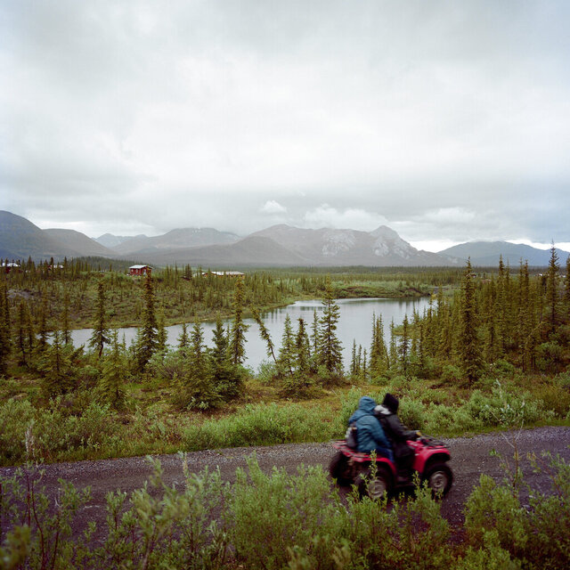 In this June 14, 2019 photo, a four-wheeler is ridden through Arctic Village, Alaska. If the pandemic has deepened the sense of isolation for the 8,000 or so Gwich'in, sprinkled across northeastern Alaska into Canada, it has also emphasized the importance of the tribe's traditions and its profound spiritual connection to the homelands that sustain the caribou and other wildlife on which they depend. (Brian Adams/Religion News Service via AP)